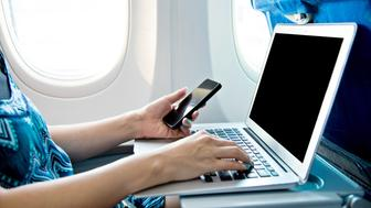 Woman using smart phone and laptop on airplane.