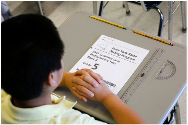 A fifth-grade student in Roosevelt, New York with the Common Core mathematics test booklet.