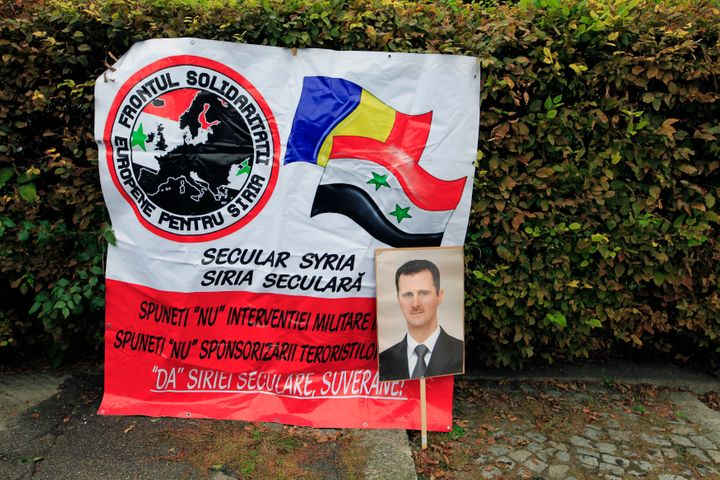 A portrait of Syrian President Bashar Assad is seen next to a banner of the European Front of Solidarity for Syria during a d