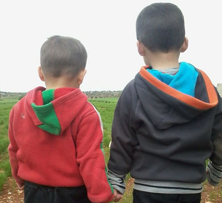 Mohammed's two twin boys walk outside near their home in Idlib.
