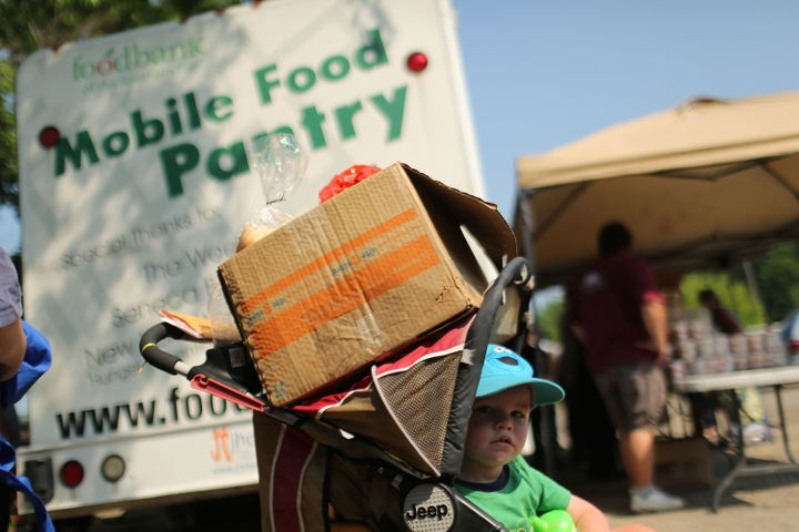 A child waits at a food bank distribution site in Oswego, New York, in 2012. Rural communities are sometimes overlooked when