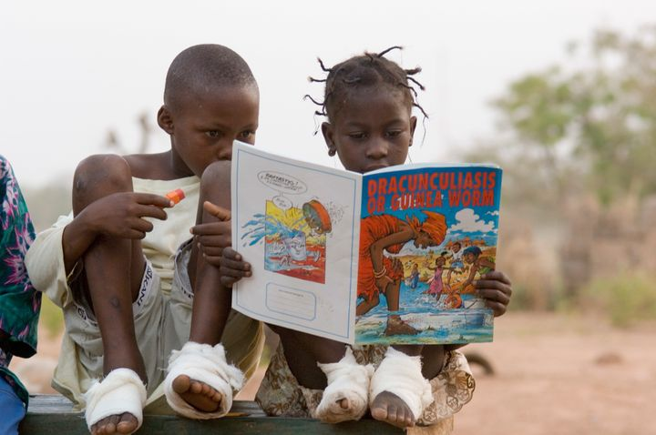 Two children, whose feet were bandaged after being treated for Guinea worm, look at an illustrated book about the diseas