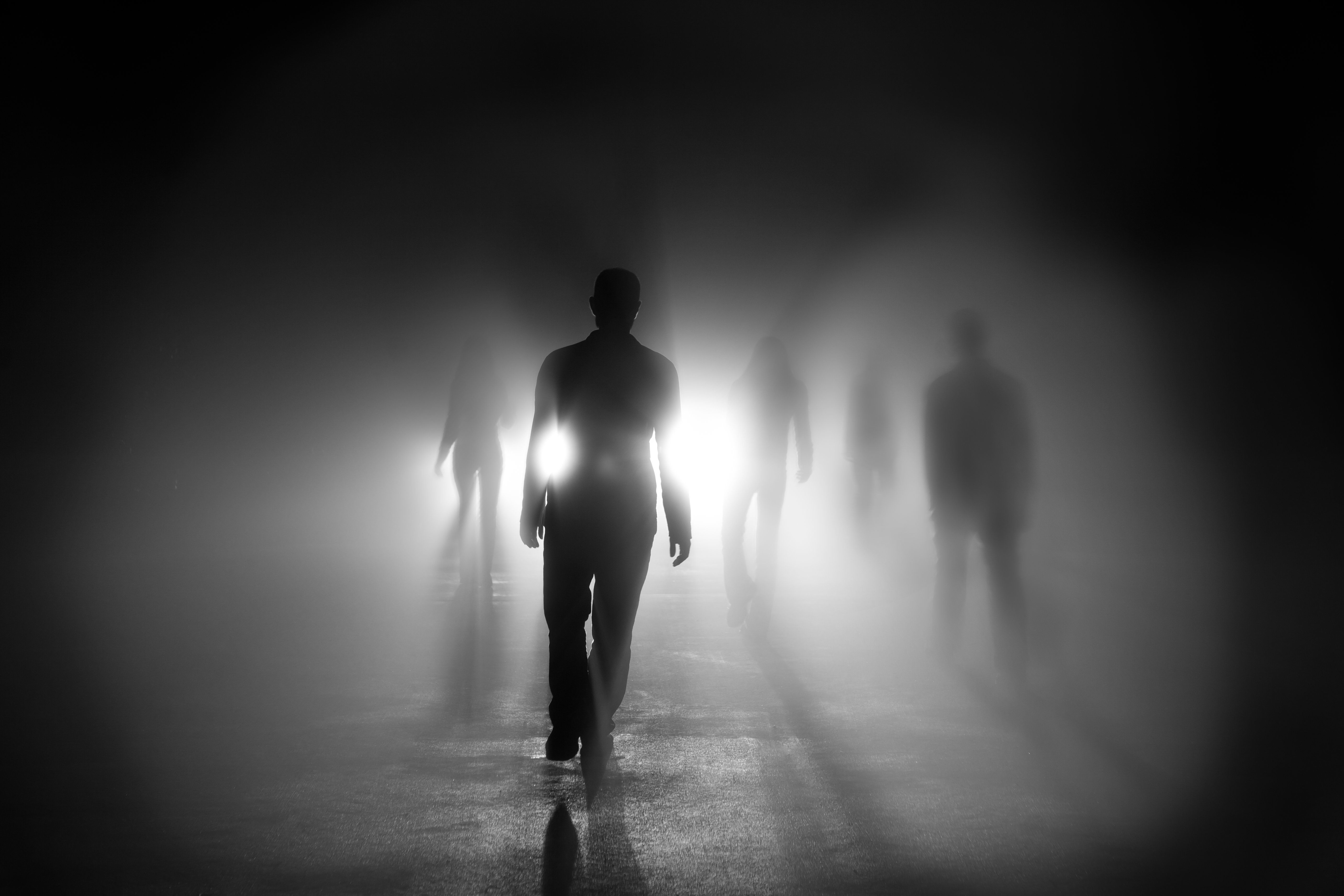 Silhouettes of 5 people walking into light with shadows.