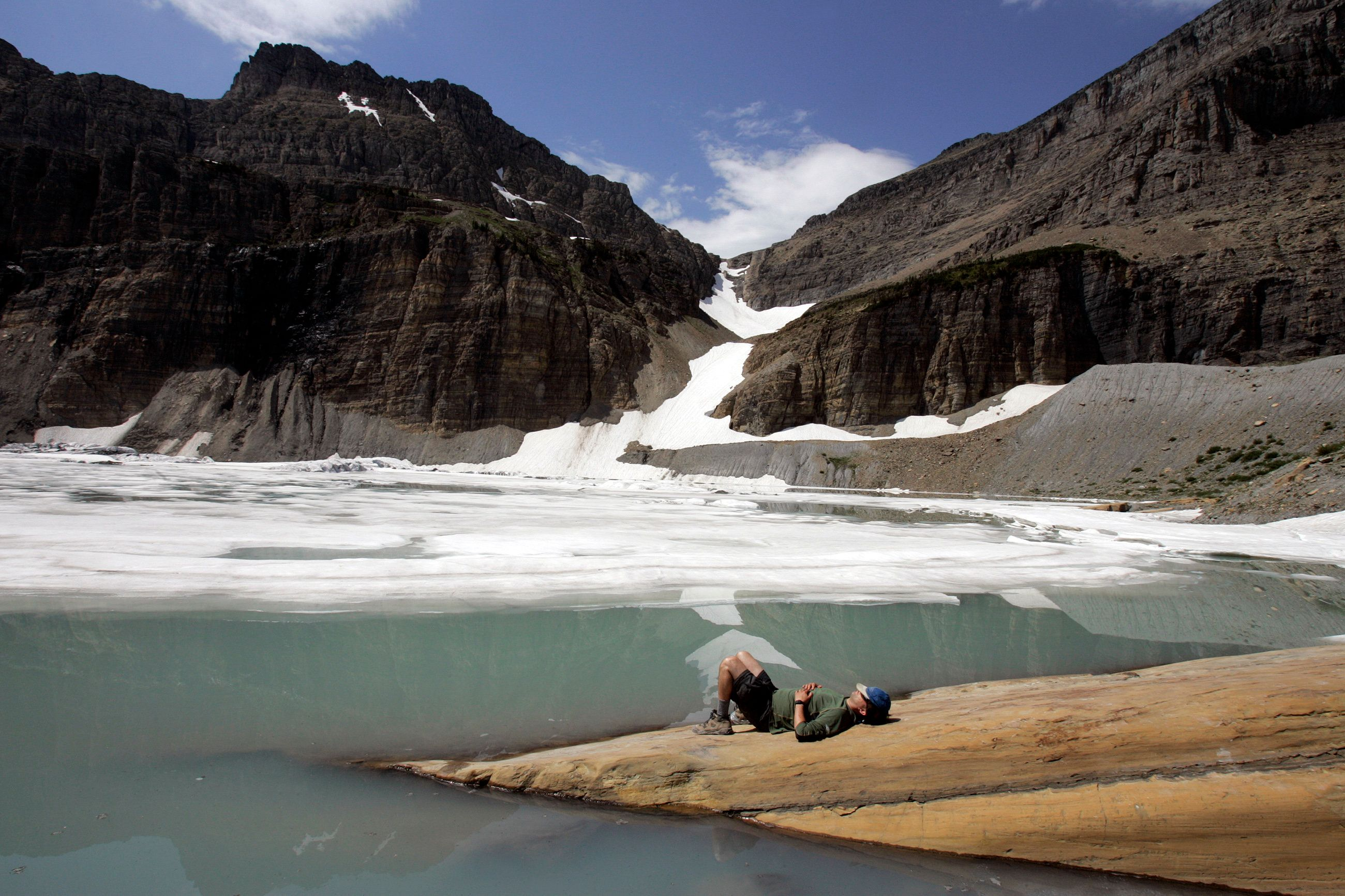 A hiker rests at the edge of the Grinnell Glacier after reaching the top of the Grinnell Glacier Trail at Glacier National Park in Montana. Photos taken in July 2006.  (Photo by Allen J. Schaben/Los Angeles Times via Getty Images)