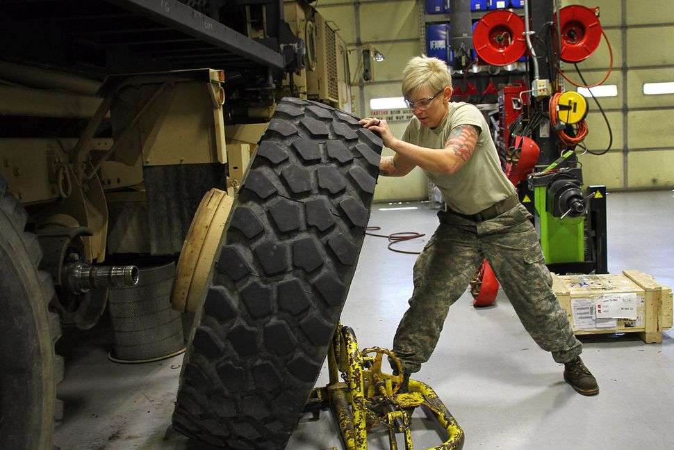 Kentucky Army National Guard Staff Sgt. Kathleen Braithwaite removes a wheel from a M977 Heavy Expanded Mobility Tactical Tru