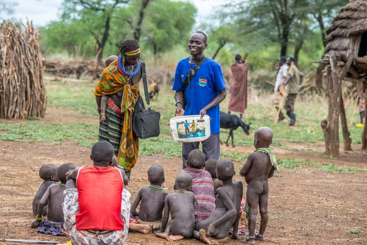 A health worker in South Sudan uses a picture book to teach children and adults how to avoid contracting Guinea worm disease.