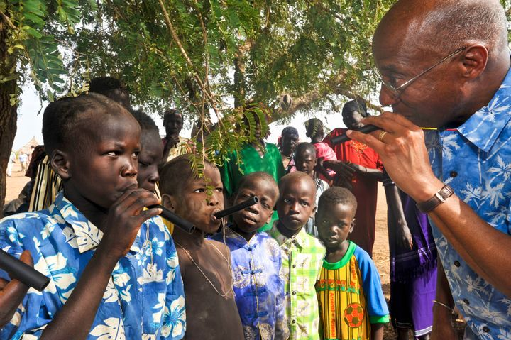 The Carter Center's Dr. Donald Hopkins shows South Sudanese children how to use plastic water filtration pipes.