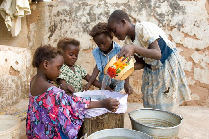 Girls who previously suffered from Guinea worm filter their drinking water to prevent the disease.
