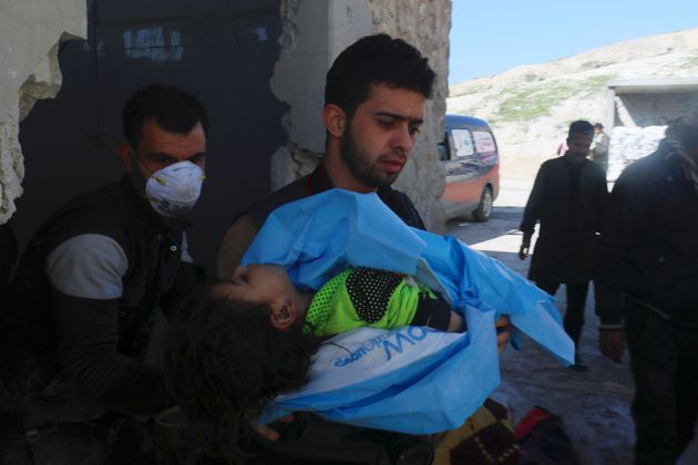 A man carries the body of a dead child, after what rescue workers described as a suspected gas attack...