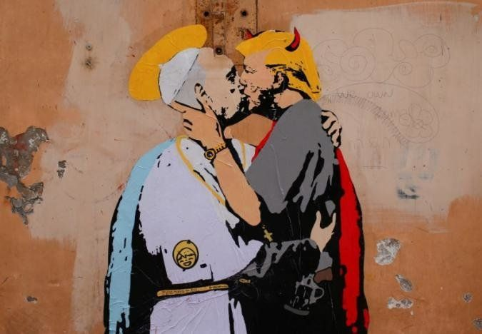 A mural signed by 'TV Boy' and depicting Pope Francis and U.S. President Donald Trump kissing, is seen on a wall in downtown