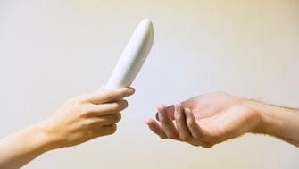 Close up of woman's hand, handing a man's hand a vibrator