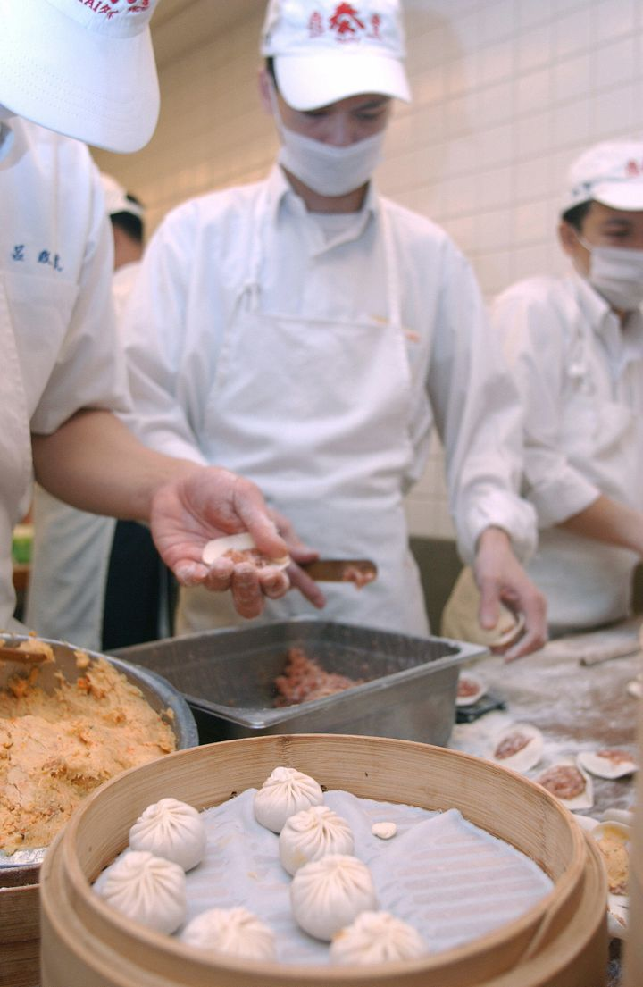 Din Tai Fung chefs fill dumplings with minced pork at the restaurant's Taiwan location.