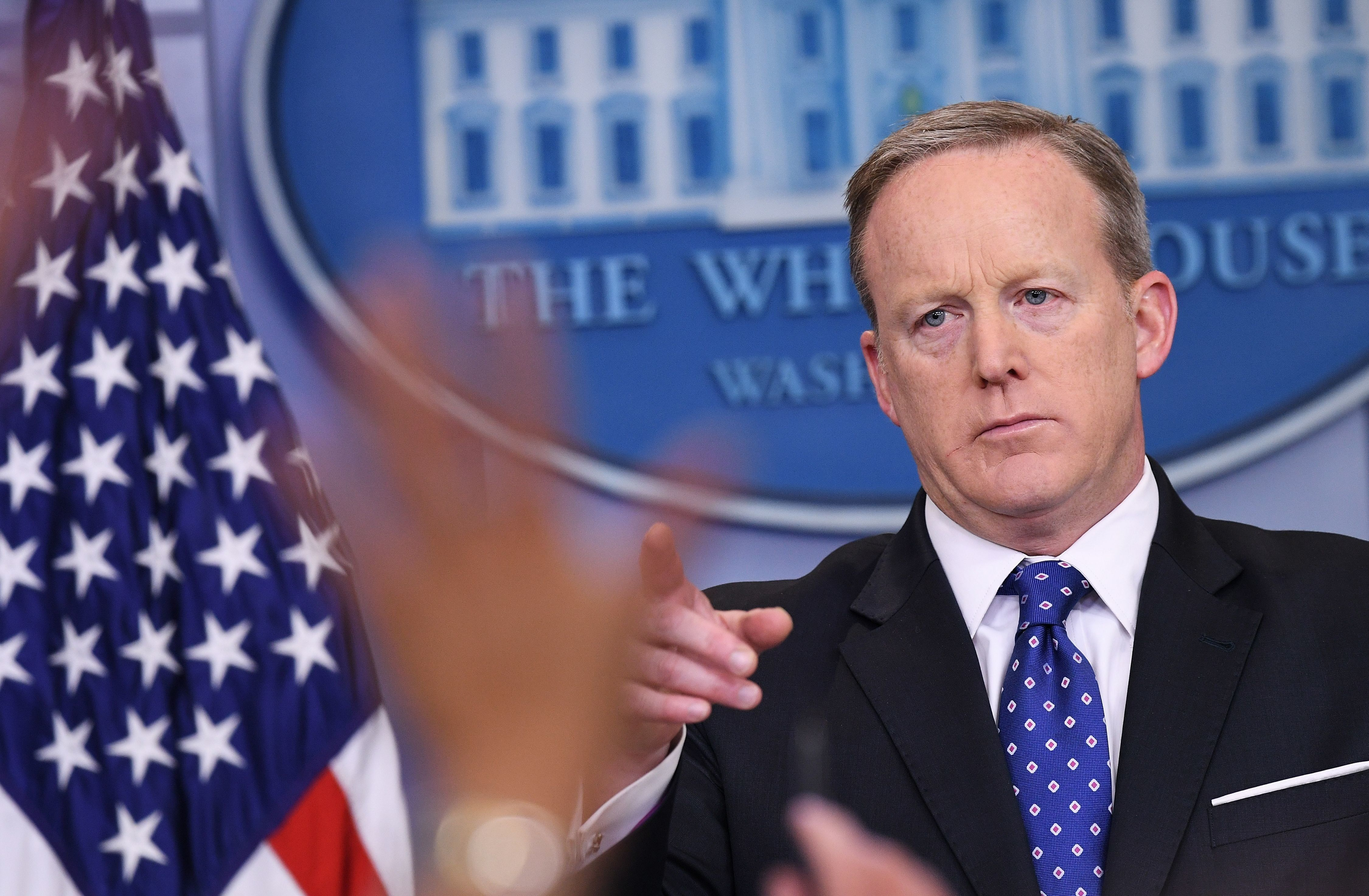 Reporters raise their hands with questions asWhite House press secretary Sean Spicer speaks during the daily briefing i