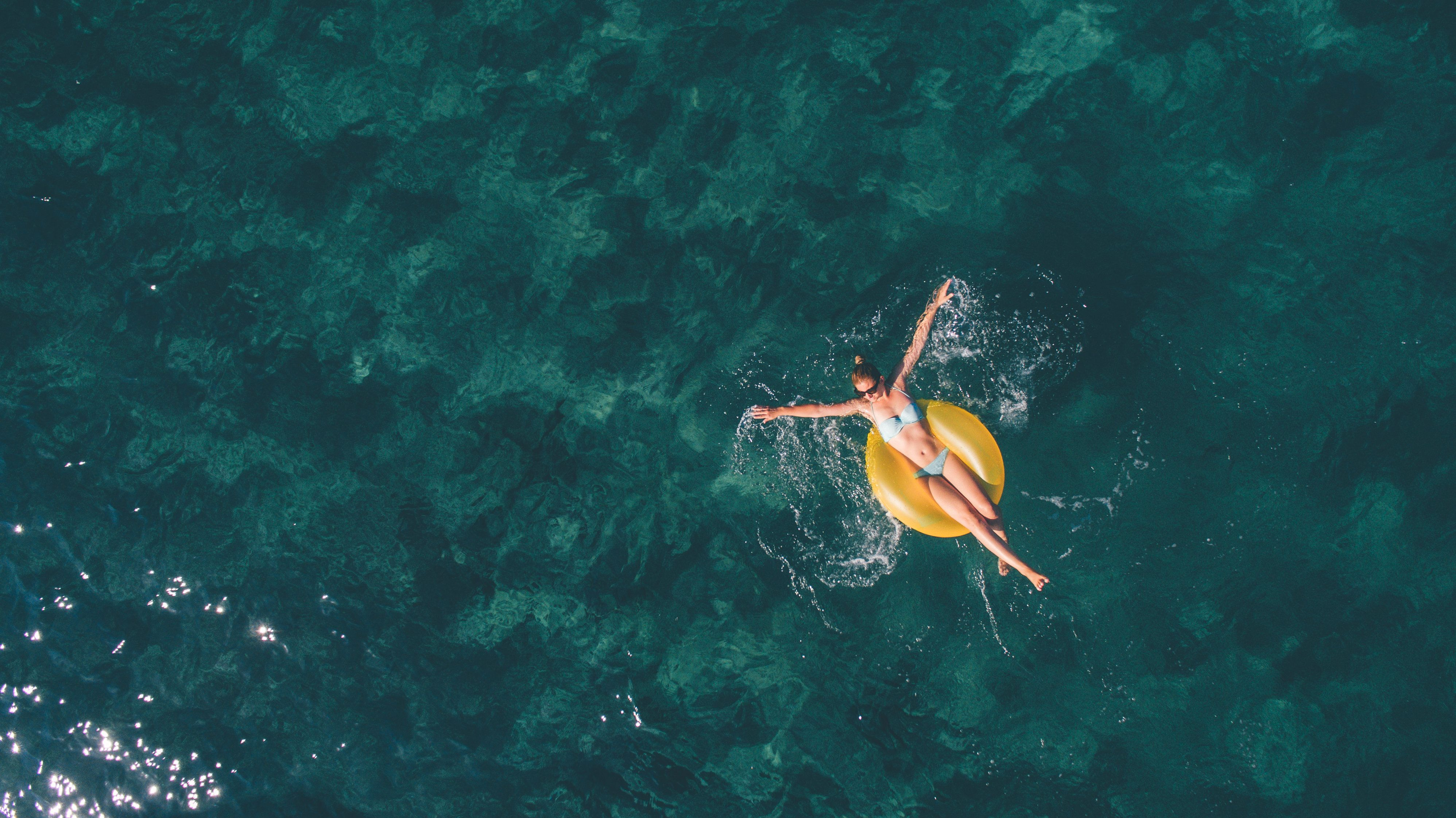 High angle view photo of a young woman relaxing while floating in the ocean using swimming tube; wide photo dimensions