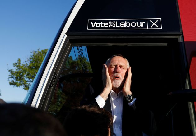 Jeremy Corbyn reacts as he gets on a bus after a campaign event in