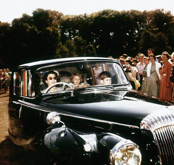 Driving her children, Prince Charles and Princess Anne, at Windsor, watched by a group of onlookers in 1957.