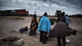 Honduran migrants warm themselves next to a campfire near the train tracks in the community of Caborca in Sonora state, Mexico, on January 13, 2017. Hundreds of Central American and Mexican migrants attempt to cross the US border daily. / AFP / ALFREDO ESTRELLA        (Photo credit should read ALFREDO ESTRELLA/AFP/Getty Images)