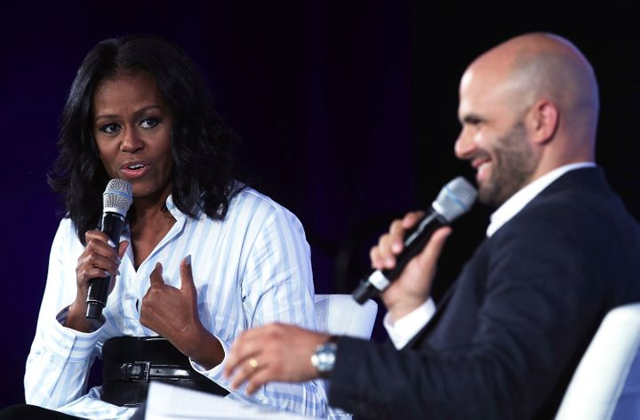 Former first lady Michelle Obama talks with former White House chef Sam Kass during the Partnership for a Healthier Amer