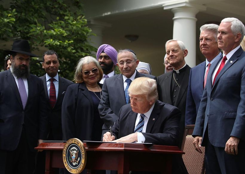 Donald Trump is flanked by clergy members as he signs an Executive Order during a National Day of Prayer event on May 4, 2017