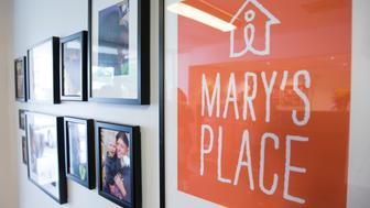 A sign for the non profit Mary's Place is pictured next to photos in a building owned by Amazon that is being used as a temporary homeless shelter for women and their families in Seattle, Washington on May 4, 2016.   According to the non profit, Marys Place is a temporary emergency family nightshelter housing up to 60 families each night, including pets. Mary's place helps homeless women, children and families to reclaim their lives by providing shelter, nourishment, resources, healing and hope in a safe community. / AFP / Jason Redmond        (Photo credit should read JASON REDMOND/AFP/Getty Images)
