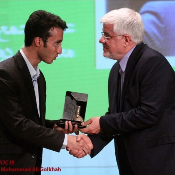 Ehsan Hamidi (L), is receiving a student award from Mohammad Reza Aref (R), a parliamentary leader of reformist faction for c