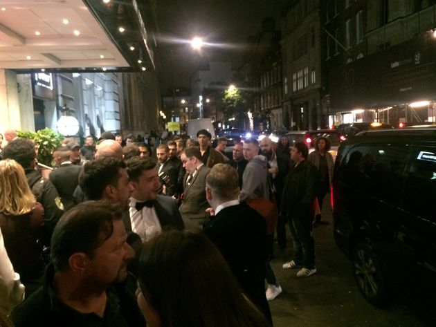 Groups of passersby and photographers crowd the entrance of the Connaught Rooms venue, left, just seconds...