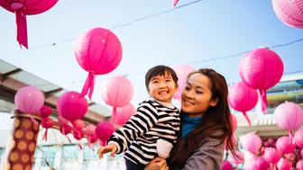 Pretty young mom carrying lovely toddler girl looking at the traditional Chinese lanterns hanging above them smiling joyfully