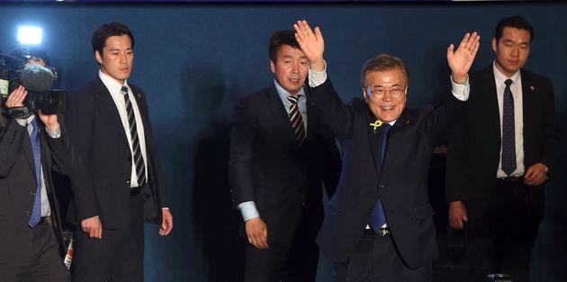 Moon Jae-in waves his hands as his bodyguards look