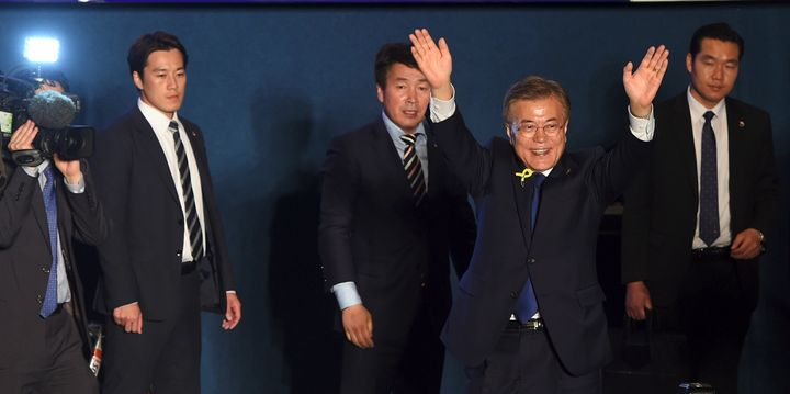 Moon Jae-in waves his hands as his bodyguards look on.