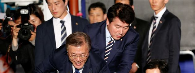 President Moon Jae-in reaches to the crowd as his now-famous bodyguard in the background looks as handsome...