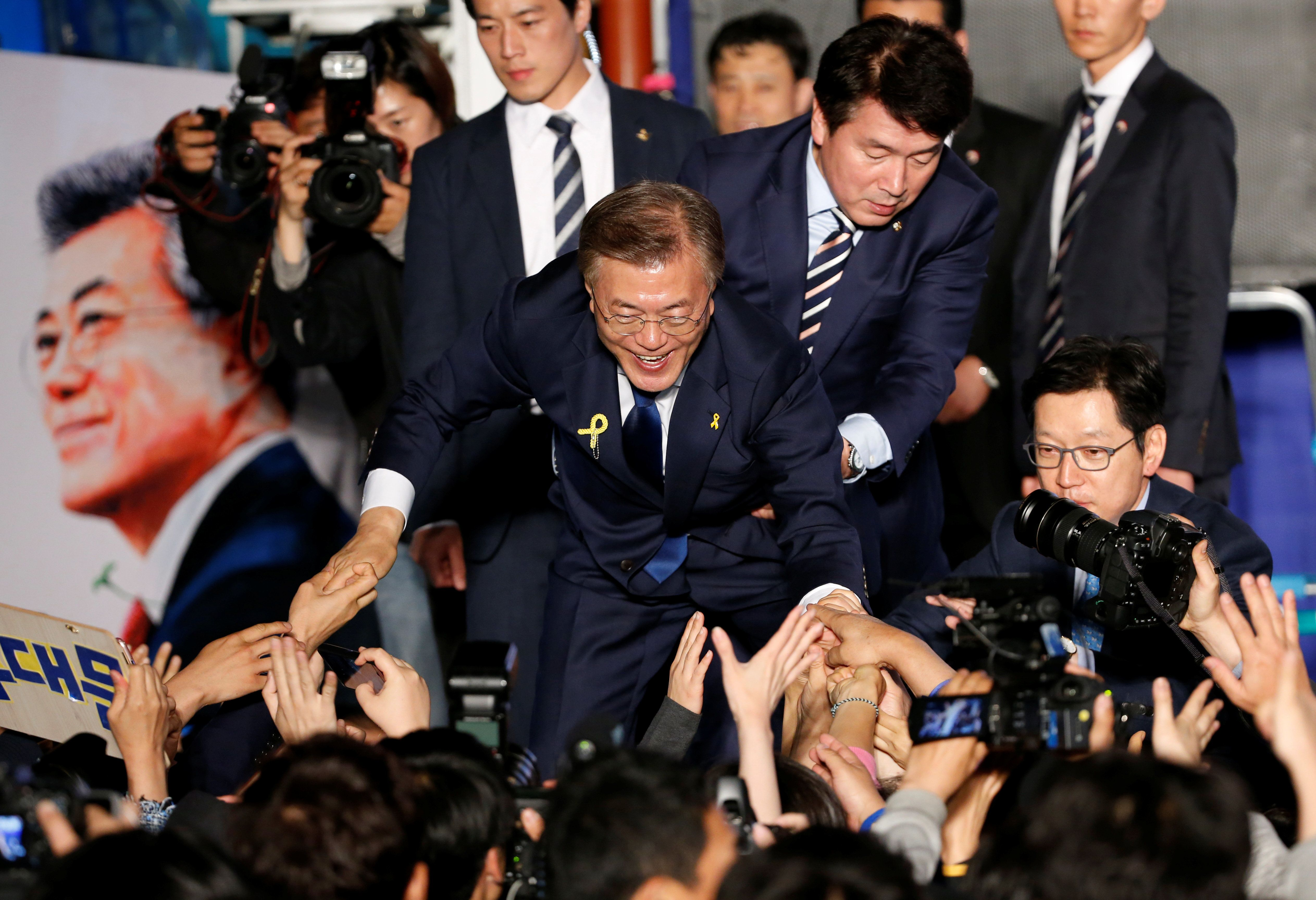 President Moon Jae-in reaches to the crowd as his now-famous bodyguard in the background looks as handsome as ever.