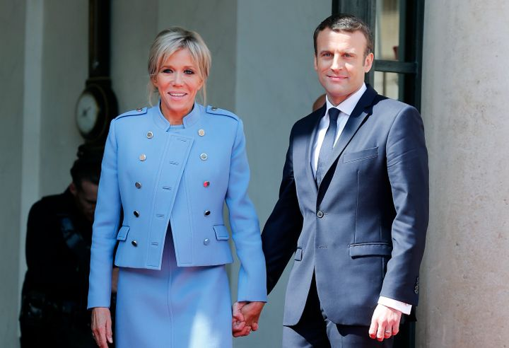 Newly-elected President Emmanuel Macron and his wife Brigitte Trogneux pose on the steps of the Elysee Palace after the hando