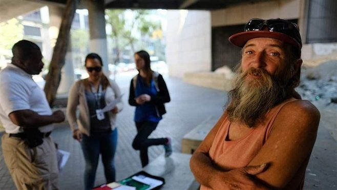 David Brophy, right, talks to representatives of a Los Angeles group who are helping him acquire an ID card on a city street