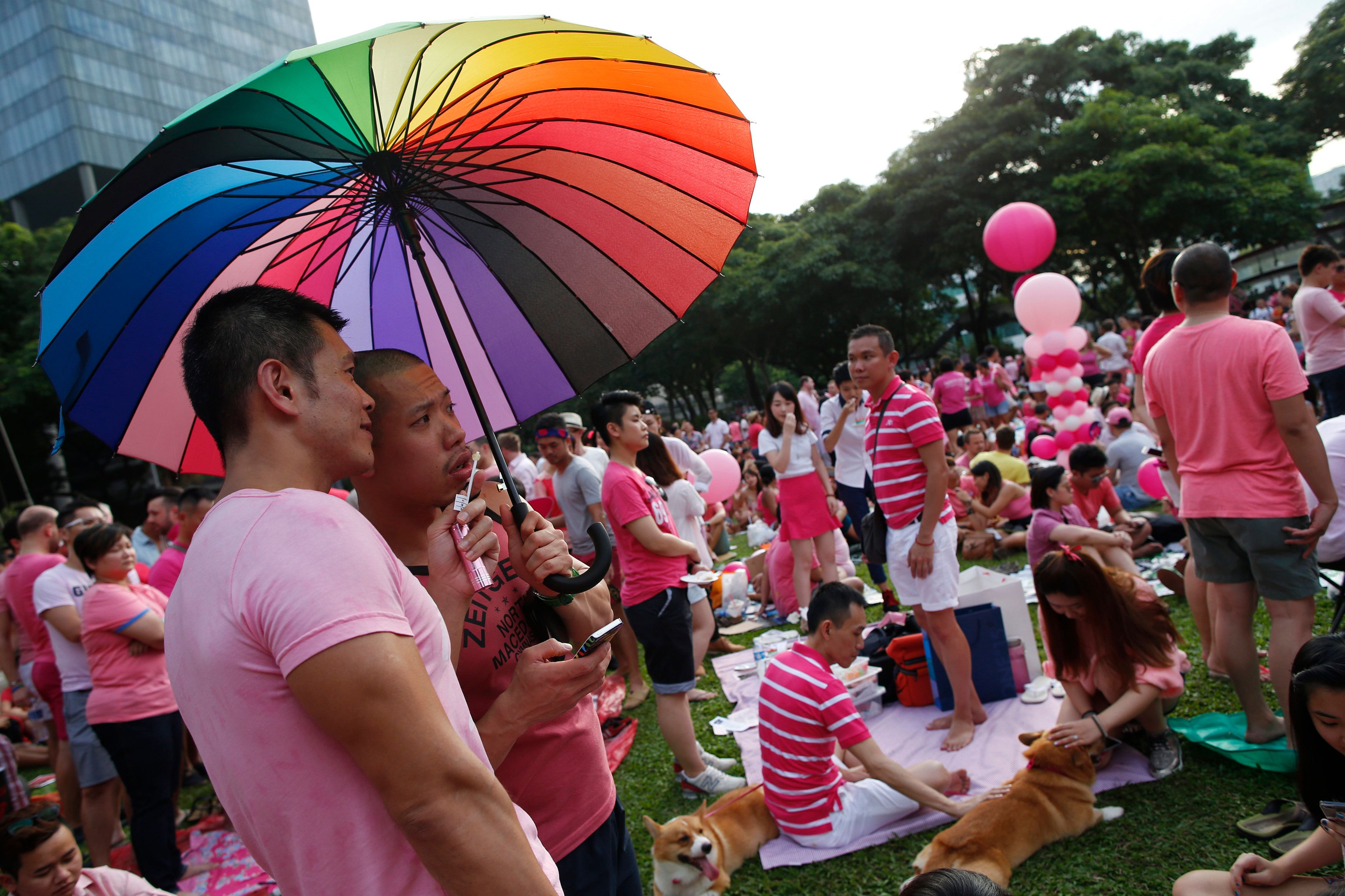 Participants dressed in pink enjoy a picnic before taking part in the forming of a giant pink dot at the Speakers' Corner in Hong Lim Park in Singapore June 28, 2014. The annual Pink Dot Sg event promotes an acceptance of the Lesbian, Gay, Bisexual and Transgender (LGBT) community in Singapore, according to organisers. REUTERS/Edgar Su (SINGAPORE - Tags: SOCIETY)