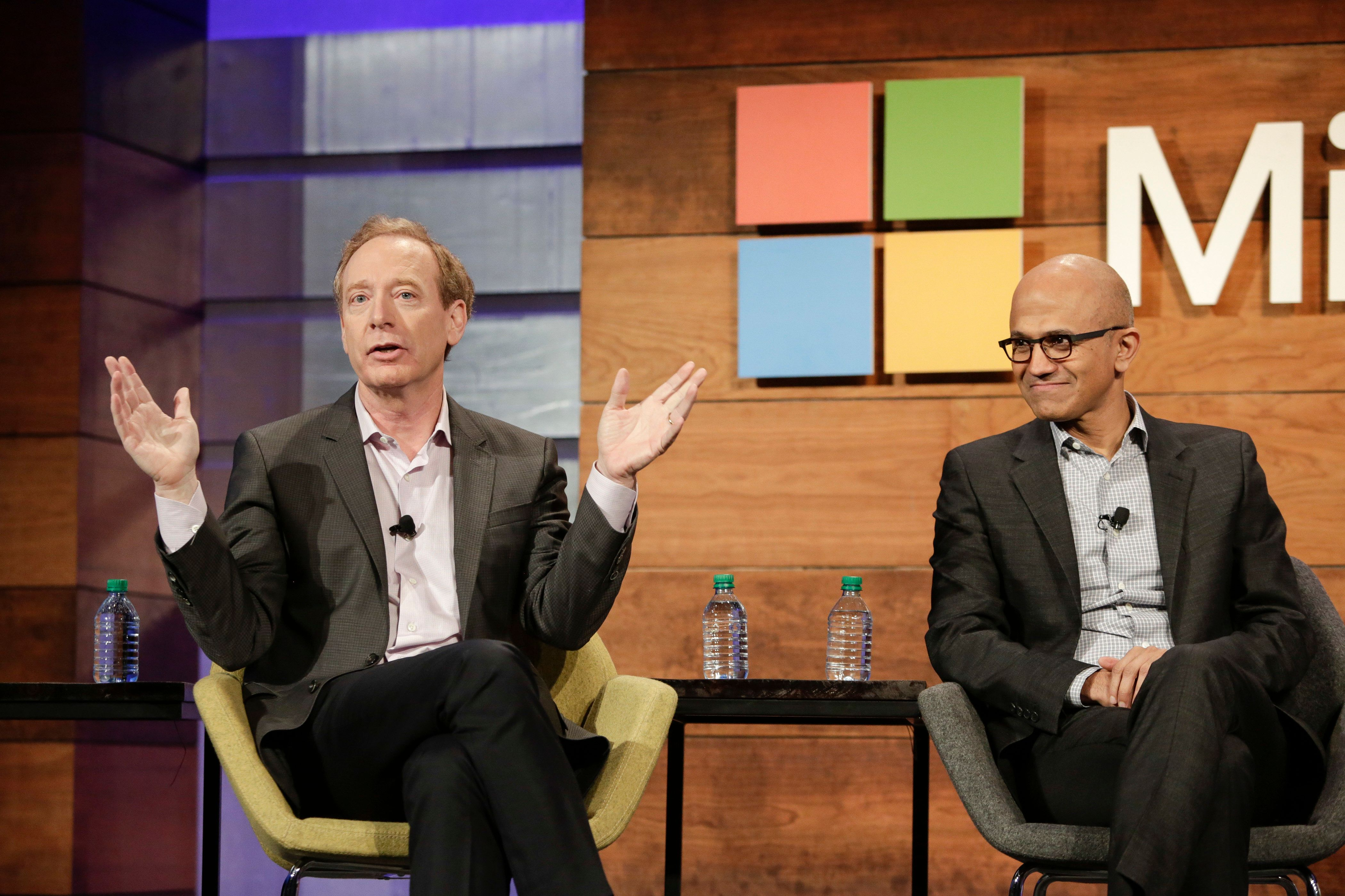 Brad Smith, President and Chief Legal Officer of Microsoft Corp., speaks as Satya Nadella, Chief Executive Officer, listens at the Microsoft Annual Shareholders Meeting in Bellevue, Washington on November 30, 2016.  / AFP / Jason Redmond        (Photo credit should read JASON REDMOND/AFP/Getty Images)