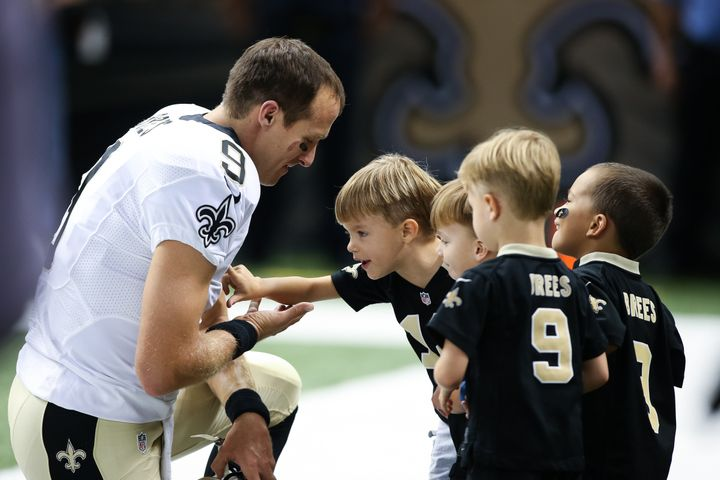 Brees pauses on the sideline with his family before an August 2015 game.