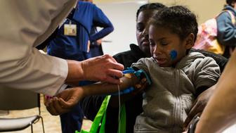 FLINT, MICHIGAN - FEBRUARY 4:  Jacob Thomas, 6, of Flint, Mich., is held by his mother Alexis Taylor, 38, as he gets his blood drawn in order to test his blood lead levels at Carriage Town Ministries in Flint, Mich., on Thursday, February 4, 2016. Thomas recently was found with elevated blood lead levels and is now having to go through additional testing. His mother said he has shown signs of behavioral problems within the last year, something she said she believes may be linked to elevated lead levels in his blood.  He and his family had been using the Flint water until December of 2015. (Photo by Brittany Greeson for The Washington Post via Getty Images)