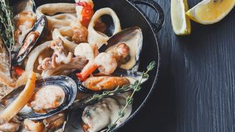 Seafood Stew in Saucepan closeup. Authentic italian restaurant cuisine, healthy delicatessen food. Oysters, shrimps, calamari in white cream sauce with bruschetta. Bowl on dark black wood background