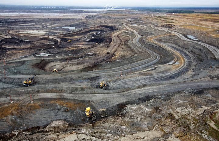 Giant dump trucks haul raw tar sands to be processed at the Suncor tar sands mining operations near Fort McMurray in Alberta,