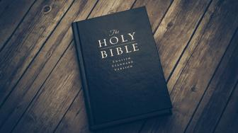 Holy Bible on wooden table.