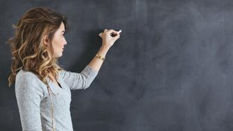 Young teacher writing on a blackboard.