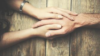 man and a woman holding hands at a wooden table