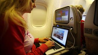 TRIVANDRUM, INDIA - DECEMBER 08:  A woman is working with a notebook and listen to music with headphones on board of a Emirates Airline passenger jet on December 08, 2009 in Trivandrum, India. Since some month its new that travelers can use the ICE System, internet by LAN, write emails or doing office work or internet shopping with a computer and a screen integrated in the seats.As well its possible to make telephone calls (Photo by EyesWideOpen/Getty Images)