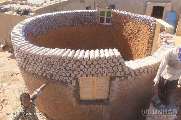 Workers construct one of the new houses, conceived by Tateh Lehbib to be weather-resistant, eco-friendly...