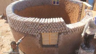 At one of the five refugee camps, host to an estimated 90,000 Sahrawi refugees near the town of Tindouf in south-west Algeria, young workers construct one of the new houses. Engineer Tateh Lehbib conceived these weather-resistant, eco-friendly homes to stand up to the sandstorms and flooding that damage houses built from traditional adobe clay bricks. ; The Sahrawi refugee situation is one of the most protracted in the world. Refugees from Sahrawi tribes fleeing conflict in Western Sahara have been living in camps in the Algerian desert since 1975. They have access to public services, roads and electricity, but living in harsh desert conditions in a remote location, the Sahrawi refugees are extremely vulnerable and entirely dependent on international assistance for survival. The scarcity of fresh food, water, insufficient education and health services have a direct impact on the population's health and wellbeing. After devastating floods damaged 17,000 houses in October 2015, UNHCR helped to fund this innovative youth construction project to build 25 houses in an aerodynamic circular shape to withstand storms.