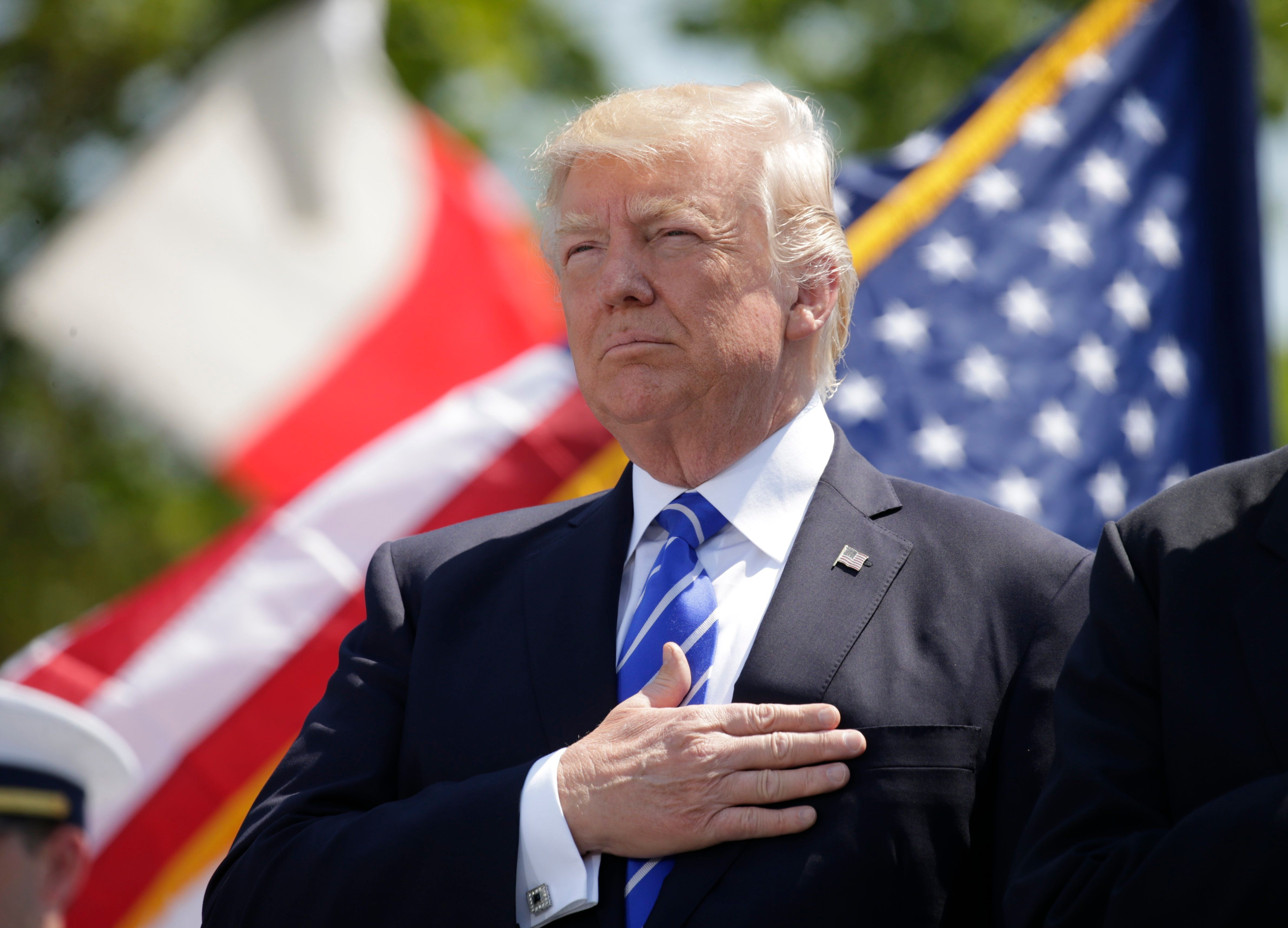 President Donald Trump holds his hand over his heart for the U.S. National Anthem as he attends the Coast Guard Academy commencement ceremonies to address the graduating class in New London, Connecticut, U.S. May 17, 2017. REUTERS/Kevin Lamarque
