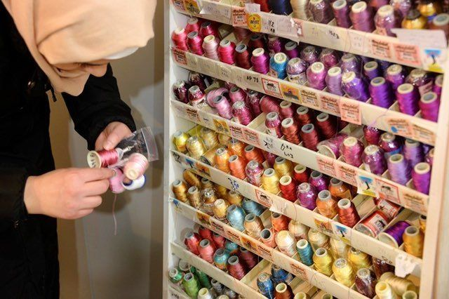 A Syrian woman selects thread to make earnings for Drop Earrings, Not Bombs, an income-generation and community-building proj