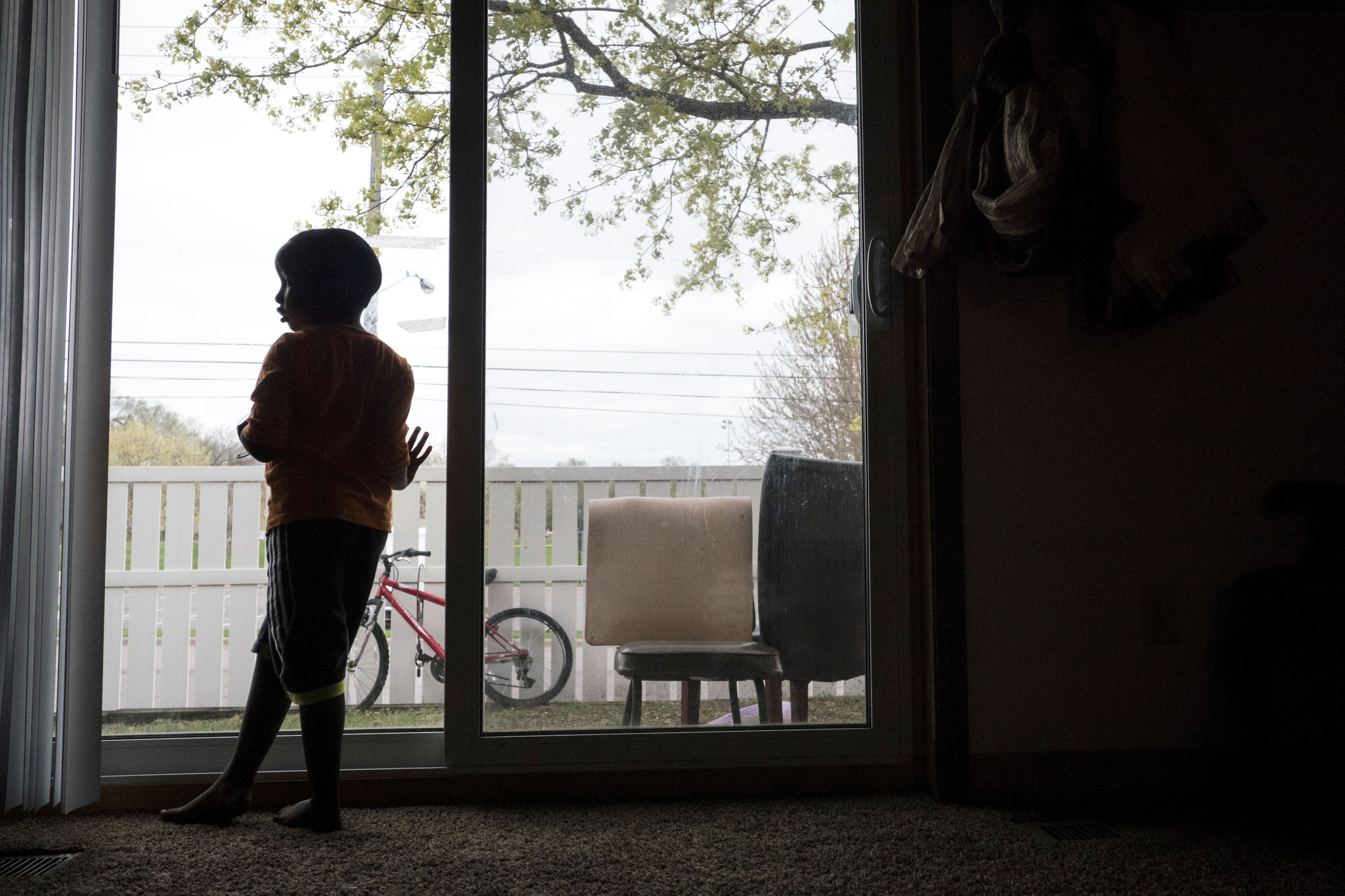 HOPKINS, MN - APRIL, 27: Abdullahi Mohamud, 5, stands by the sliding glass door in his family's apartment in Hopkins, Minn., Thursday April 27, 2017. Though two of his siblings contracted the measles during the current outbreak in Minneapolis and are now recovering at home, he received one dose of the vaccine in January and did not get sick. The children must wait until May 7, when the incubation period is over, to return to school. (Photo by Courtney Perry/For the Washington Post)
