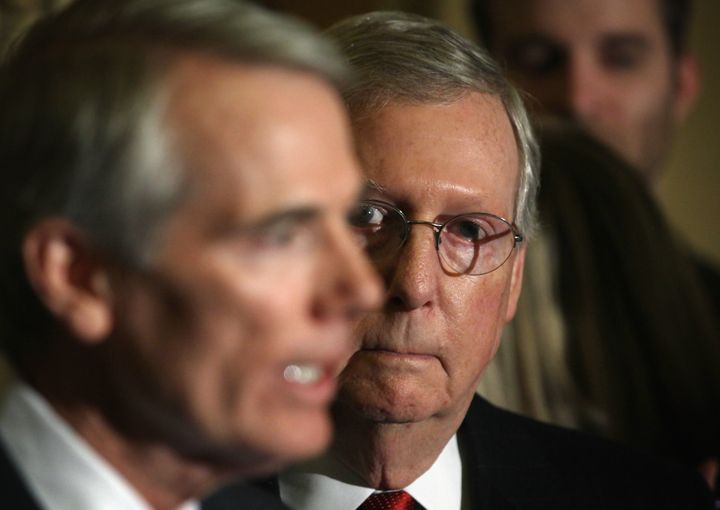 Senate Majority Leader Sen. Mitch McConnell listens as Sen. Rob Portman (L) speaks during a media briefing after the Senate R