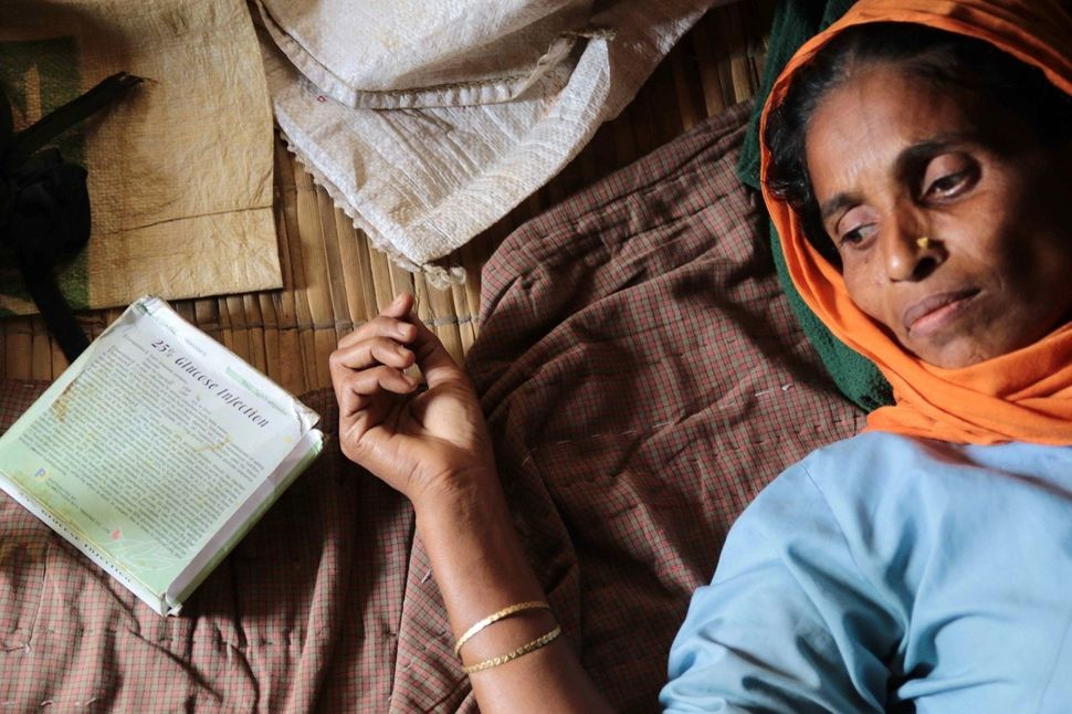 Rucia Begum awaits treatment. She lives in a recently constructed hut with six other members of her family, including her mot